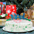 Christmas cake in front of Christmas tree and gifts. — Stock Photo