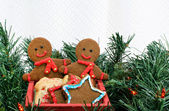 Two gingerbread men in cart among Christmas greens with copy space. — Stock Photo