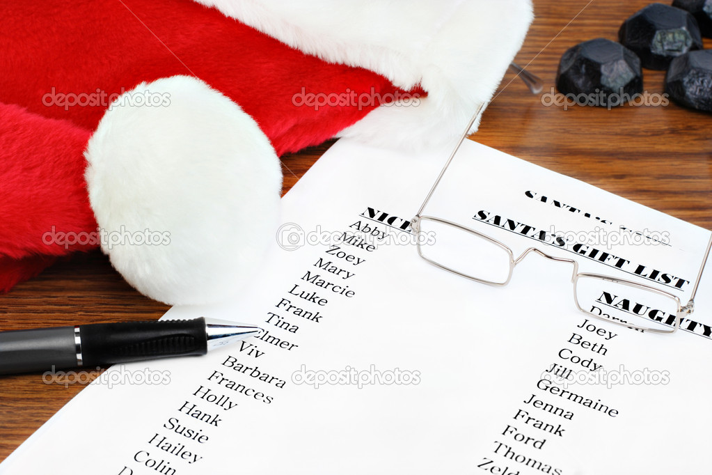 Santa's naughty and nice gift list on a table with his hat and glasses.  Stock Photo #7565196