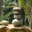 Pile of pebble Stones against the background of palm trees and the sea - Stock Photo