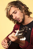 若い男、ギターと笛を吹く — ストック写真