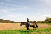 Equestrienne gallops on hillside. — Stock Photo
