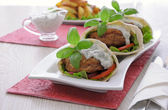 Patty in pita bread with cream sauce and vegetables — Stock Photo