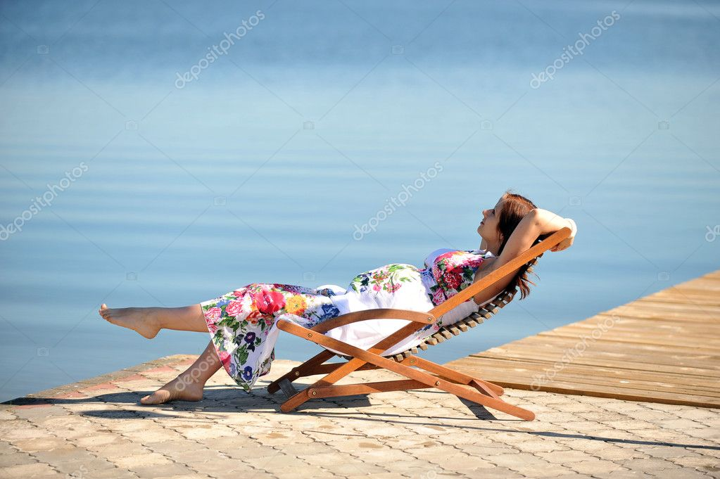 Woman sitting in  lounge chair. summer's day on lakeside — Stock Photo #6933273
