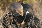 Camouflaged war photojournalist. — Stock Photo