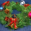 Nice Xmas decorations: red, silver and blue spheres, golden bells with red ribbon and green Xmas wreath over blue - Stock Photo