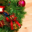 Nice Xmas decorations: red sphere, golden bells with red ribbon, red candle and green Xmas wreath over wooden desk - Stock Photo