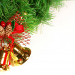Royalty-Free Stock Photo: Nice golden bells with red ribbon and green xmas tree brunch over white
