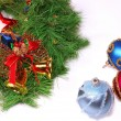 Nice Xmas decorations: red, silver and blue spheres, golden bells, red candle and Xmas wreath over white — Stock Photo