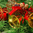 Golden bells against Xmas tree branch - Stock Photo