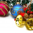 Nice Xmas decorations: red and blue spheres, golden bells and garland over white — Stock Photo #7619308
