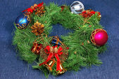 Nice Xmas decorations: red, silver and blue spheres, golden bells with red ribbon and green Xmas wreath over blue — Stock Photo