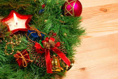 Nice Xmas decorations: red sphere, golden bells with red ribbon, red candle and green Xmas wreath over wooden desk — Stok fotoğraf