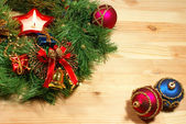 Nice Xmas decorations: red and blue spheres, golden bells, red candle and Xmas wreath over wooden desk — Stock Photo