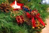 Lindo verde navidad guirnalda de oro, las campanas con cinta roja y vela roja — Foto de Stock