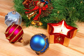 Nice Xmas decorations: red, silver and blue spheres, golden bells, red candle and Xmas wreath over wooden desk — Zdjęcie stockowe
