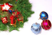 Nice Xmas decorations: red, silver and blue spheres, golden bells, red candle and Xmas wreath over white — Stockfoto