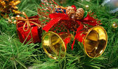 Golden bells against Xmas tree branch — Stock Photo