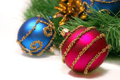 Nice Xmas decorations (red and blue spheres, golden cone and Xmas tree brunch) over white — Stock Photo