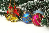Nice Xmas decorations: red and blue spheres, golden bells and garland over white — 图库照片