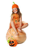 Smiling little girl sits on a pumpkin — Stock Photo