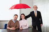 Agent assurant la couverture d'assurance pour un jeune couple — Photo