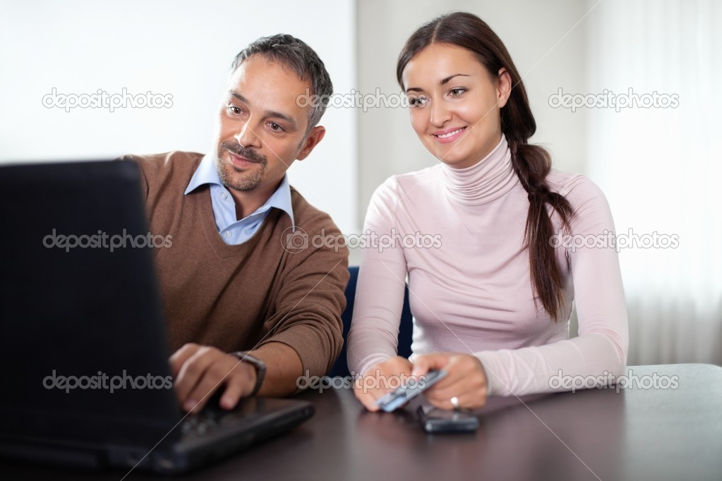 Beautiful young woman sitting with a man using laptop at office. — Stock Photo #6930564