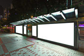 Blank billboard on bus stop at night — 图库照片