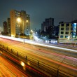 Light trails on modern city at night — Stock Photo