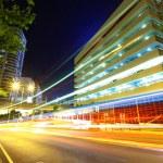 Light trails on modern city at night — Stock Photo
