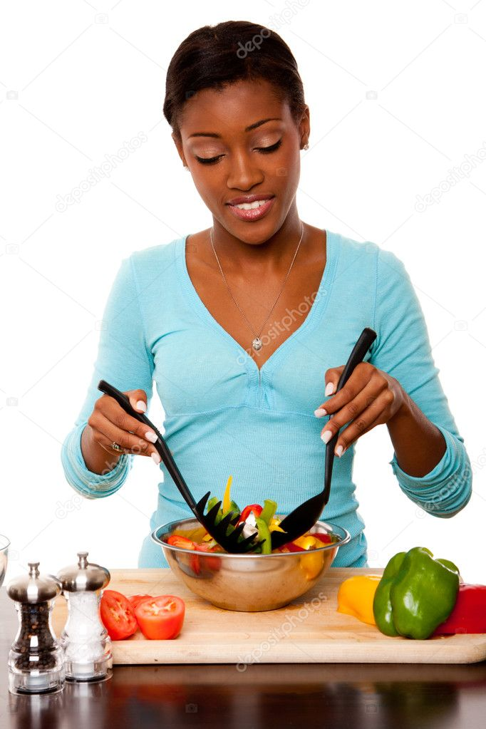 Beautiful health conscious young woman tossing healthy organic salad in kitchen, isolated. — Foto Stock #6839085