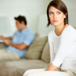 Upset young woman sitting with her husband in background - 