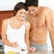 Happy young couple eating fruit salad in the kitchen - Foto Stock