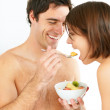 Royalty-Free Stock Photo: Young man feeding fruit salad to his wife