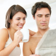 Royalty-Free Stock Photo: Attractive young couple reading newspaper