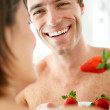 Royalty-Free Stock Photo: Happy young couple eating strawberries together