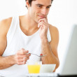 Royalty-Free Stock Photo: Young guy taking breakfast while using laptop