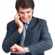 Young business man checking time while speaking on cellphone - Stock Photo