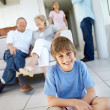 Royalty-Free Stock Photo: Little boy sitting on floor with his parents in backgropund