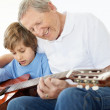 Royalty-Free Stock Photo: Small boy getting guitar lessons from his grandfather