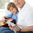 Royalty-Free Stock Photo: Happy little boy and grandfather playing guitar together