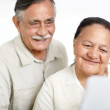 Closeup of a smiling old couple working on laptop - Stock Photo