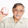 Royalty-Free Stock Photo: Closeup of a happy senior man holding piggybank