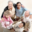 Happy group of old friends standing in a huddle - Stock Photo