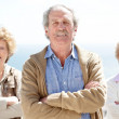 Royalty-Free Stock Photo: Handsome mature man standing with friends in background