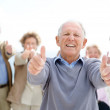 Joyful mature man showing thumbs up sin with his friends at back - Stock Photo