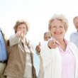 Royalty-Free Stock Photo: Happy old woman pointing at you with her friends at back
