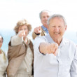 Royalty-Free Stock Photo: Happy old man pointing at you with his friends in background