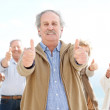 Royalty-Free Stock Photo: Senior man showing thumbs up sign with friends