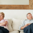 Senior woman and her husband looking away after an argument - Stock Photo